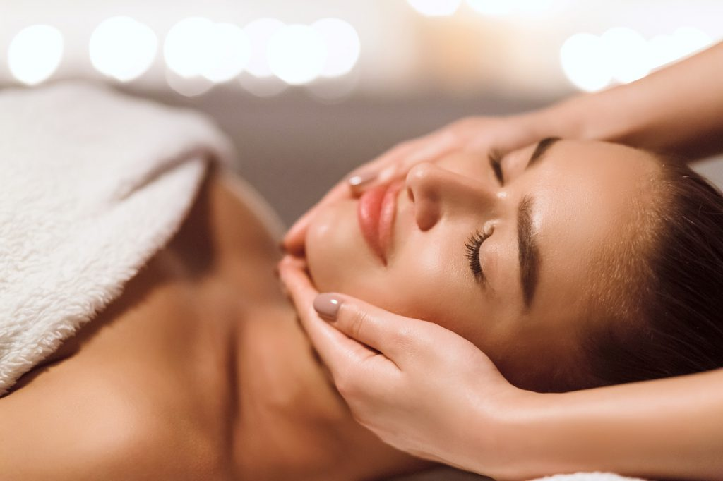 Facial Beauty Treatment. Woman Getting Face Massage